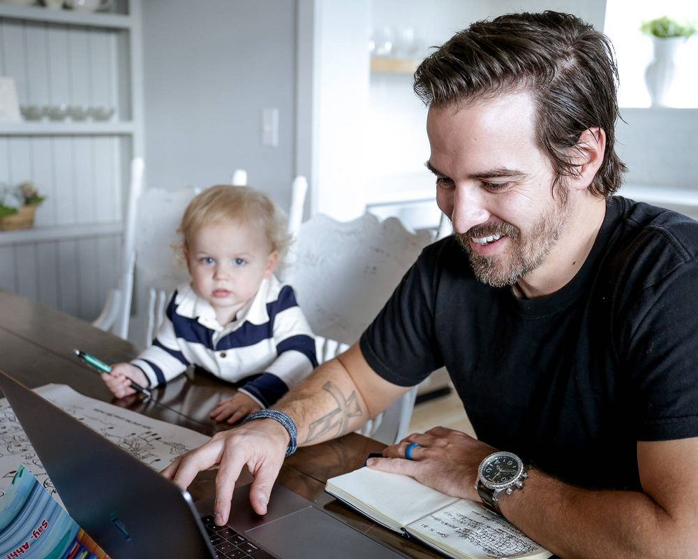 A man looking at his laptop and sitting next to his toddler-aged child