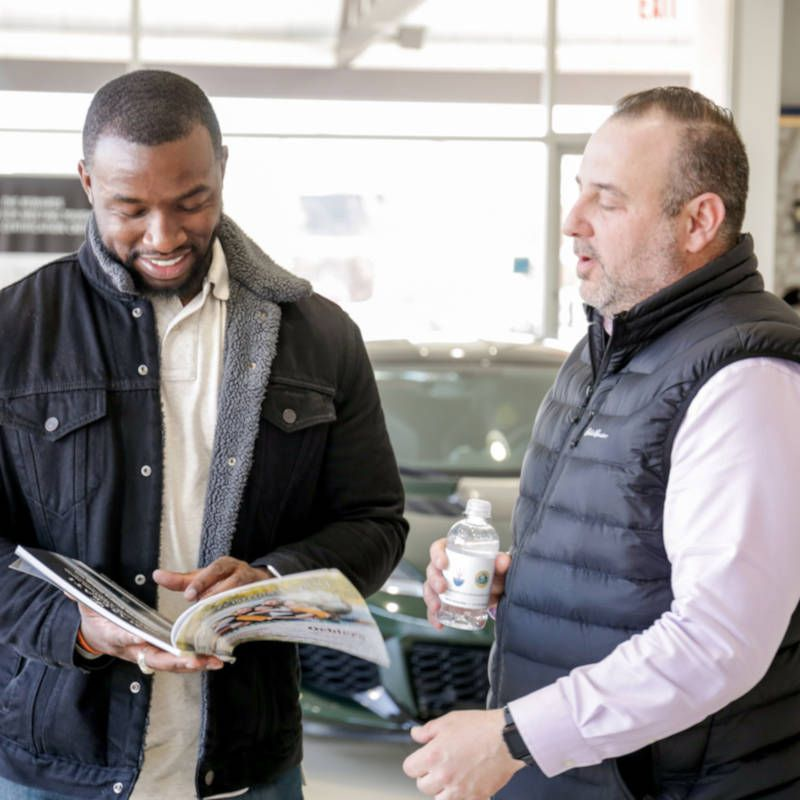 A man holding a magazine as another man looks on.