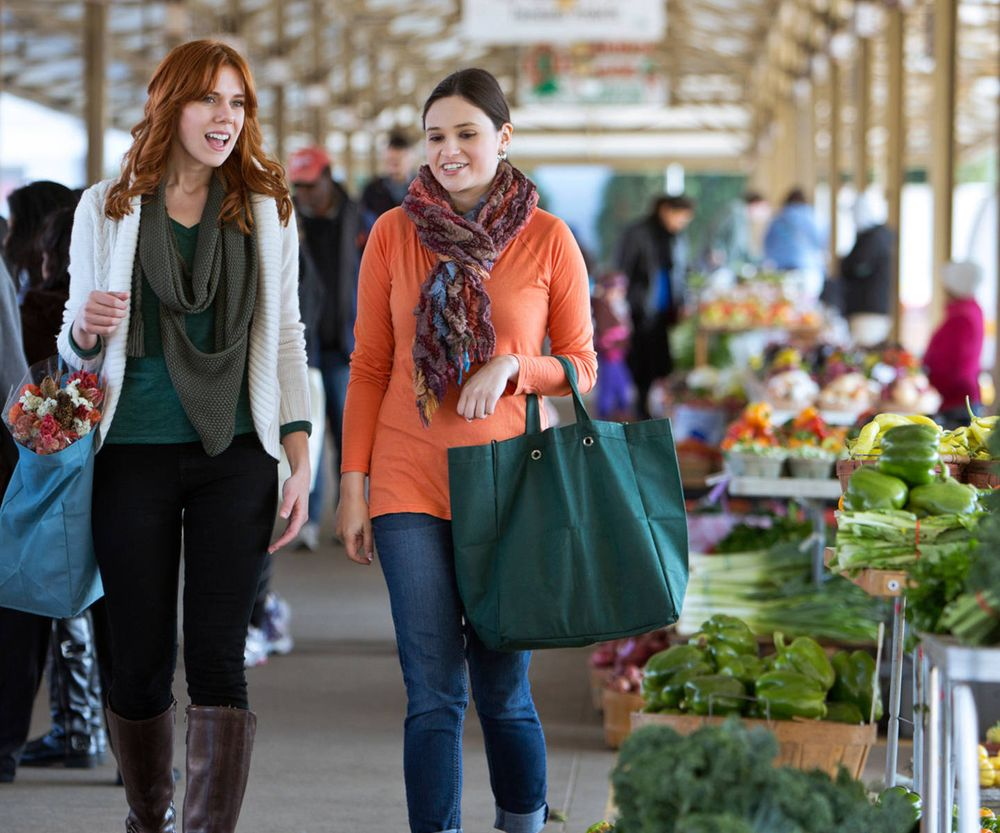 Two women walking together in a farmer's market and chatting