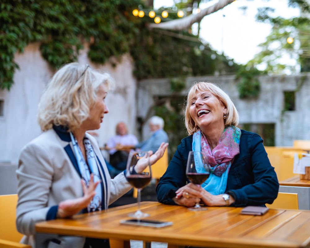 Two women sitting at a table outdoors, chatting and laughing